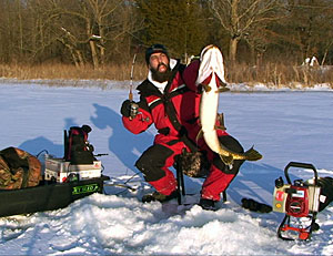 Keith Stanton with a giant Northern Pike he jigged through the ice from a Michigan lake