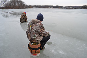 Two ice anglers search for the ice fishing bite on a lake
