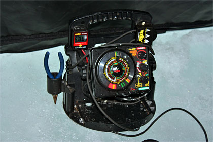 Ice fishing expert Dan Zatarga uses a flasher to verify the depth of his lure and to watch for approaching whitefish. Photo Credit: Jeff Nedwick