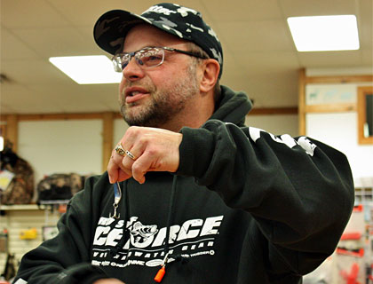 Ice fishing school leader Mark Martin demonstrates the proper way to position a treble hook on a jigging spoon