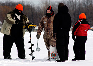 Ice anglers using some of the tools to open holes through the ice - a power auger and simple scoop