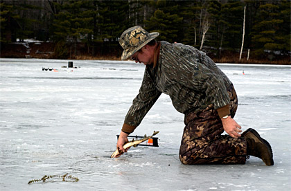 Ice fisherman releasing a small Northern Pike back through the ice