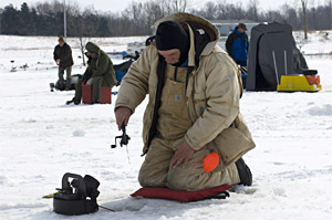 Anglers ice fishing in the open with ice fishing rod and reel
